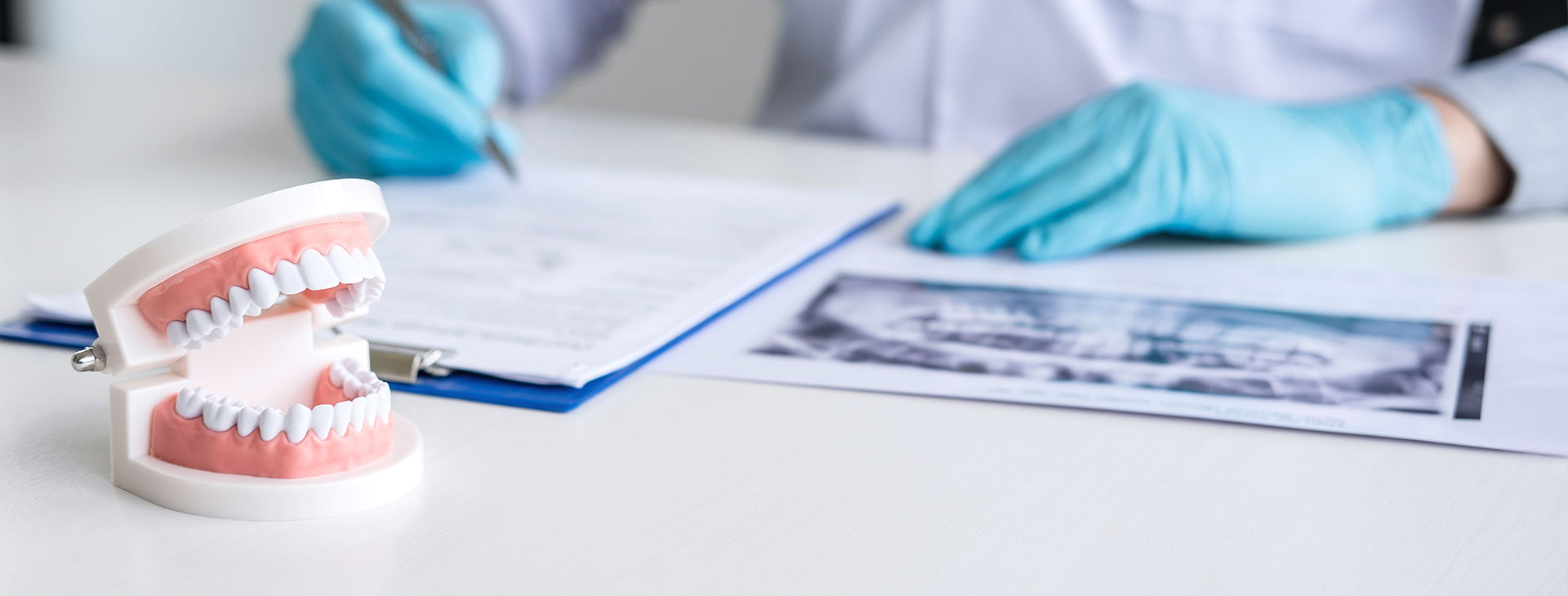 Doctor writing a report with a dental x-ray on the table