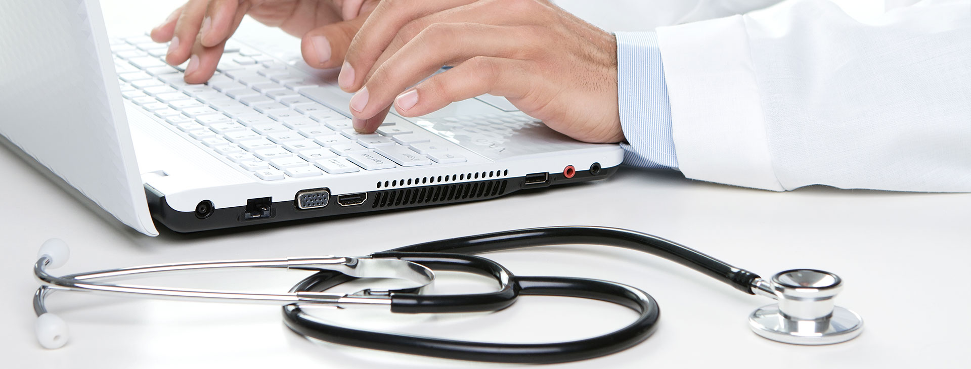 A doctor typing on his laptop at his clinic