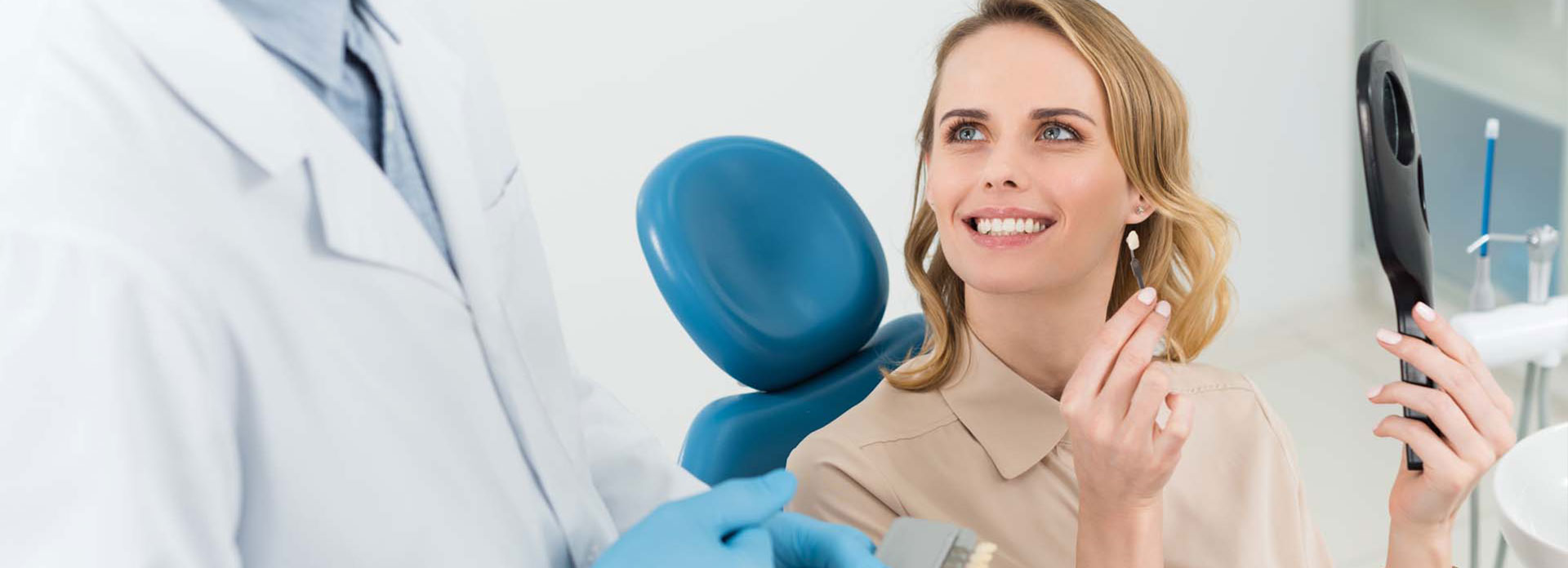 A patient smiling at the dentist after checking her teeth in the mirror