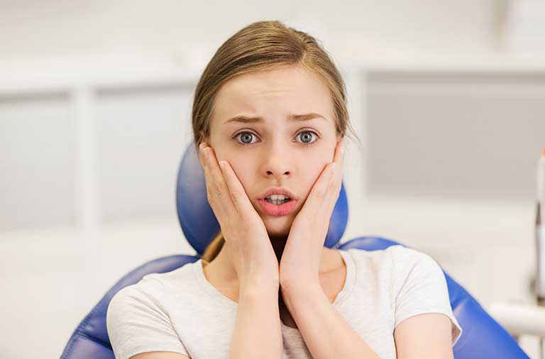 Scared and terrified patient girl at dental clinic